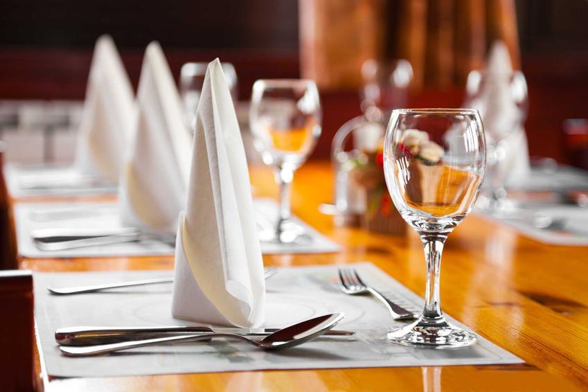 Serwetki złożone w trójkąty na talerzach na stole, a także jak złożyć serwetkę krok po kroku