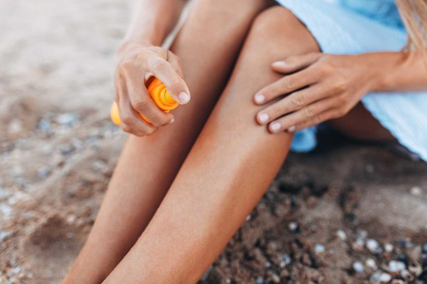 Filtr do opalania rozprowadzany na nogach przez kobietę w niebieskiej sukience, a także wybór i siła działania filtrów do opalania