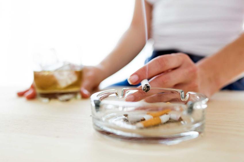 Kobieta paląca papierosy przy popielniczce, a także jak rzucić palenie krok po kroku i 4 najlepsze sposoby na rzucenie palenia