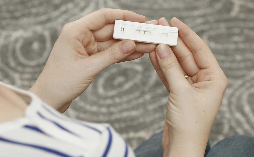 Kobieta trzymająca pozytywny test ciążowy w rękach, a także po jakim czasie zrobić test ciążowy krok po kroku