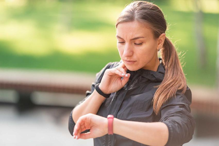 Kobieta mieżąca sobie puls na szyi po bieganiu w parku, a także jaki powinien być puls - tabela norm dla dzieci i dorosłych