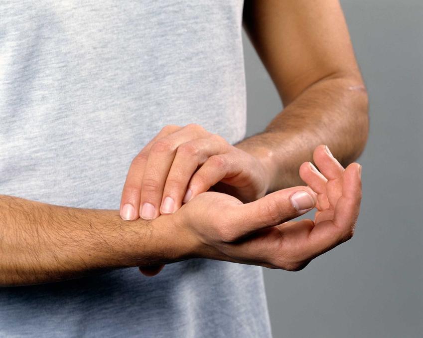 Mężczyzna mieżący sobie puls na nadgarstku, a także informacje, jakie powinien być puls dla dzieci i dorosłych, porady i przyczyny problemów z pulsem