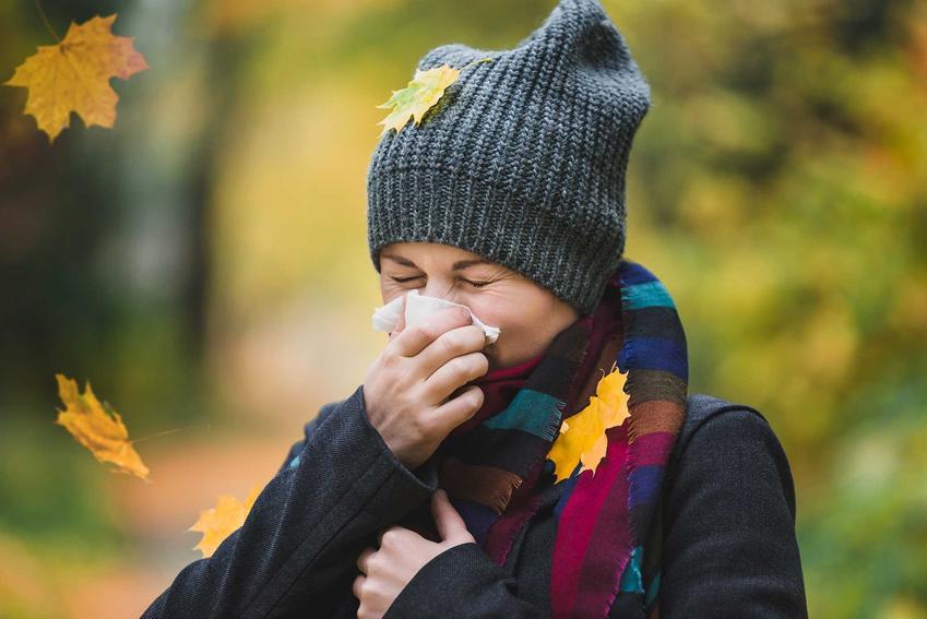 Kobieta z chusteczką przy nosie z powodu kataru w jesiennej scenerii, a także jak odetkać nos domowymi sposobami krok po kroku