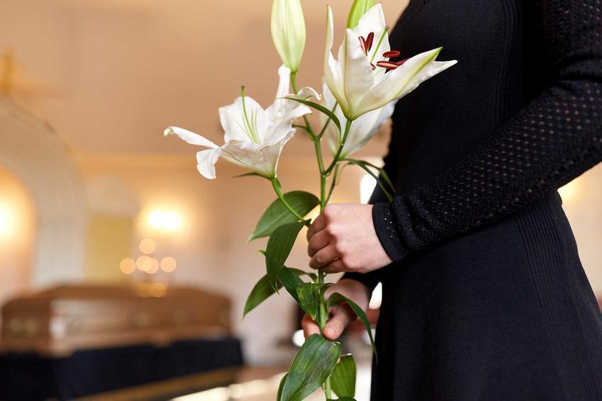 Kobieta w czarnej sukience składająca lilie na grobie podczas pogrzebu, a także informacje, jaki ubiór na pogrzeb dla bliższej i dalszej rodziny