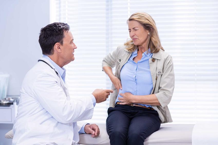 Kobieta skarżąca się na ból wątroby u lekarza, a także sposoby na szybką regenerację wątroby, leczenie i domowe metody