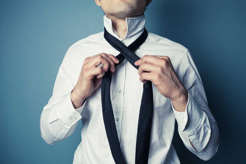 Mężczyzna zawiązujący ciemny krawat, a także jak zawiązać krawat krok po kroku - proste i popularne sposoby na wiązanie krawatu