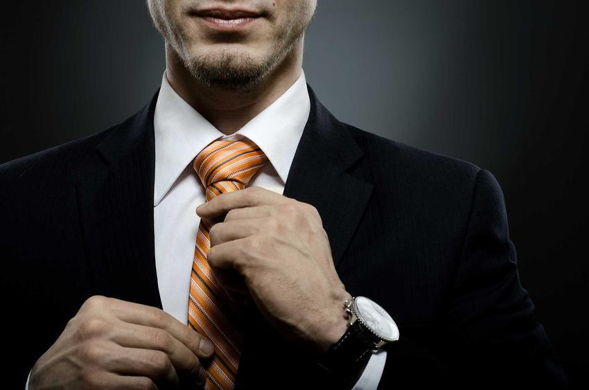 Mężczyzna poprawiający krawat, a także jak zawiązać krawat krok po kroku, proste i popularne węzły