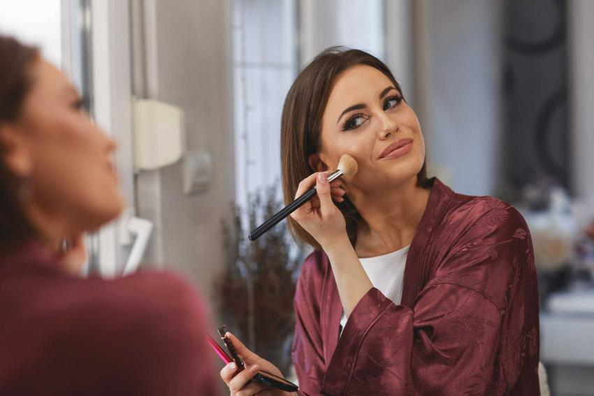 Kobieta oglądająca się w lustrze podczas nakładania różu na twarz, a także jak nakładać róż krok po kroku, najlepszy poradnik