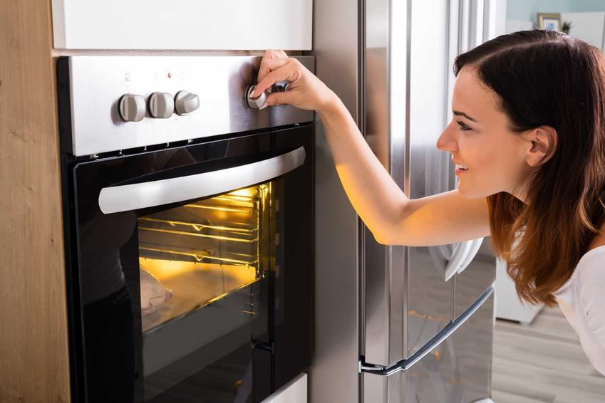 Kobieta piecząca szynkę w piekarniku, a także praktyczny poradnik, jak upiec szynkę w piekarniku krok po kroku, najlepsze przepisy