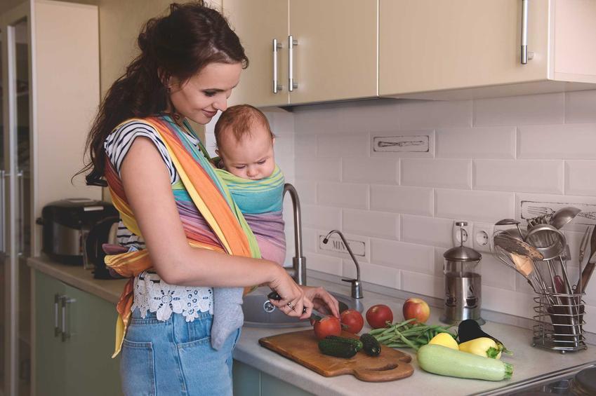 Kobieta z dzieckiem w chuście podczas krojenia owoców, a także informacja, jakie owoce można jeść podczas karmienia piersią