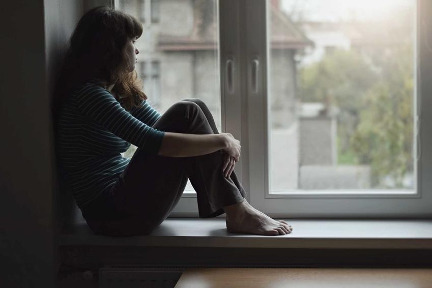 Kobieta siedząca na parapecie i odczuwająca smutek po rozstaniu, a także jak poradzić sobie z rozstaniem - 5 najlepszych sposobów