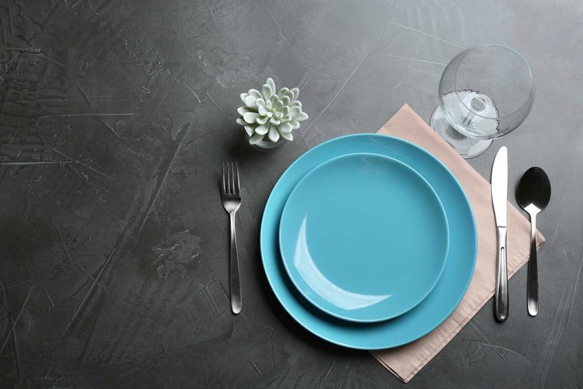 Sztućce ułożone na stole przy niebieskim talerzu, a także, jak układać sztućce na stole - najlepsze porady i zasady savoir-vivre