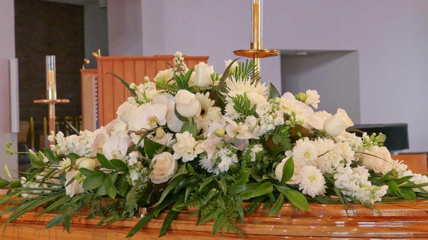 Wiązanka pogrzebowa z białych róż leżąca na trumnie, a także podpowiedzi, jakie wiązanki pogrzebowe wybrać, ich rodzaje oraz ceny