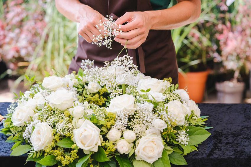 Kwiaciarka przygotowująca wiązankę pogrzebową z białych róż, a także jakie wiązanki pogrzebowe wybrać, rodzaje oraz ich ceny