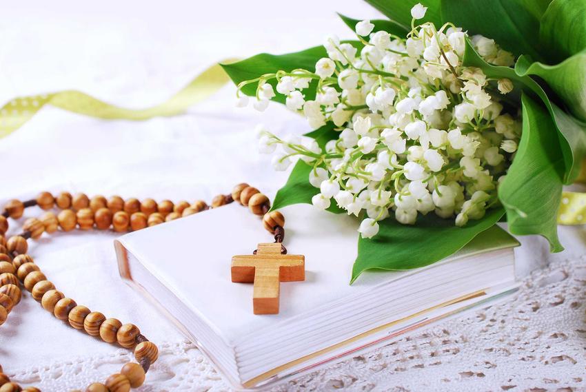 Bukiet konwalii obok drewnianego różańca i książeczki do nabożeństwa, a także najpiękniejsze wiązanki i wianki komunijne