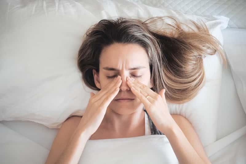 Kobieta cierpiąca na katar z powodu uczulenia na roztocza, a także jak działają roztocza i jak pozbyć się roztoczy z pościeli