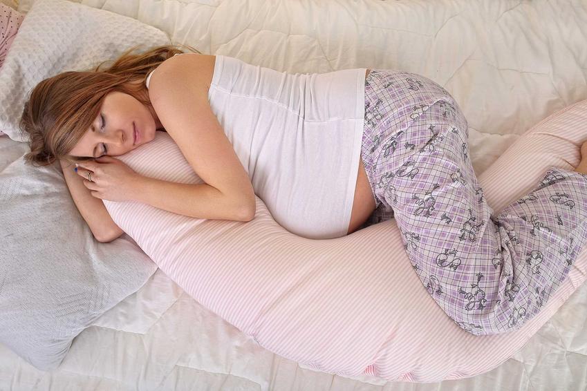 Kobieta w ciąży śpiąca na poduszce typu rogal, a także najzdrowsze i najlepsze pozycje do spania krok po kroku