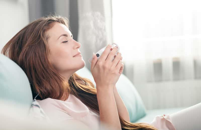 Kobieta rozkoszująca się oczyszczonym powietrzem, a także oczyszczanie powietrza krok po kroku, najważniejsze porady, odświeżacze