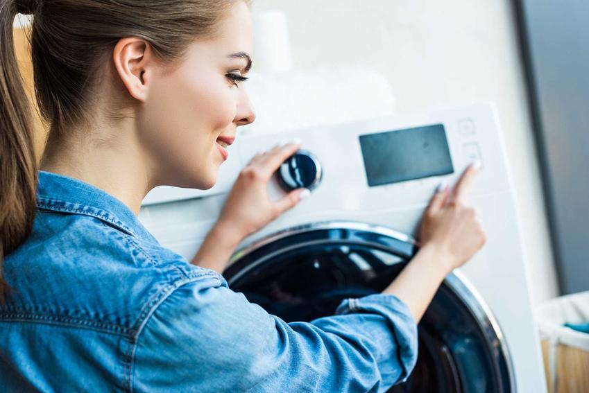 Kobieta nastawiająca program prania, a także informacje, jakie błędy najczęściej są popełniane podczas prania ubrań