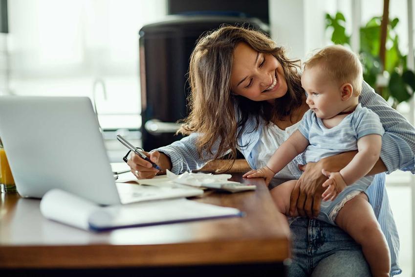Kobieta obliczająca podatek PIT z dzieckiem na kolanach, a także przegląd odliczeń na dziecko i ulg podatkowych dla rodziców