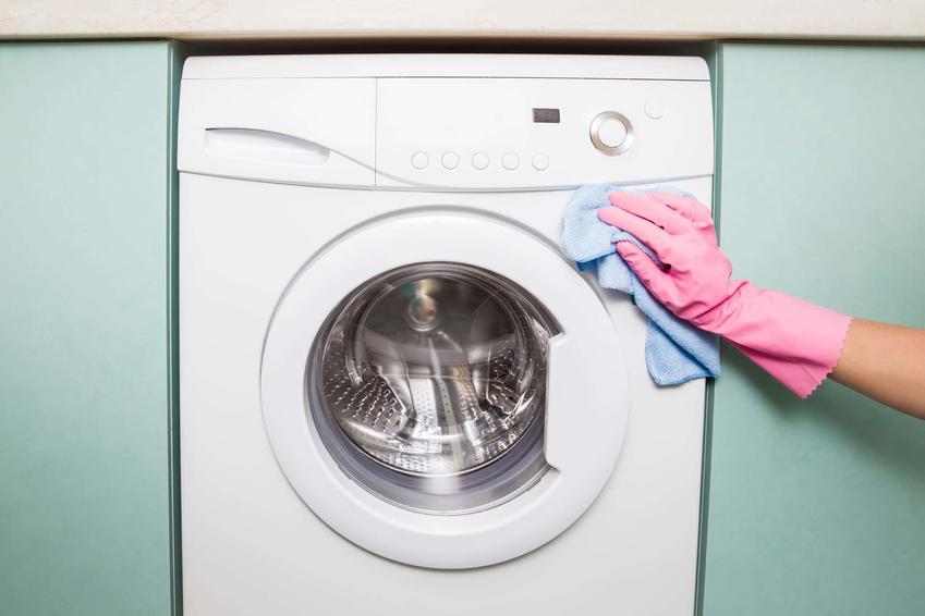 Pani w różowej rękawiczce wyciera szmatką pralkę, 5 zasad czyszczenia wnętrza pralki, środki do czyszczenia brudnej pralki