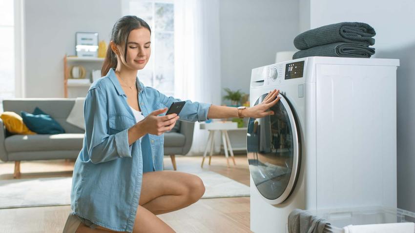 Kobieta kuca przed pralką sprawdzając telefon, poradnik jak czyścić zabrudzoną pralkę, czy da się idealnie wyczyścić pralkę