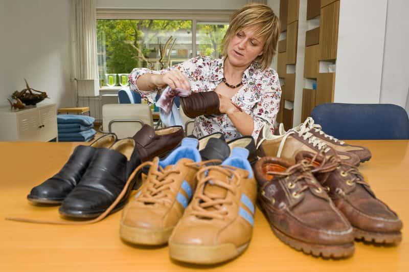 Kobieta czyszcząca buty z nubuku ściereczką, a także informacje, jak wyczyścić buty z nubuku krok po kroku