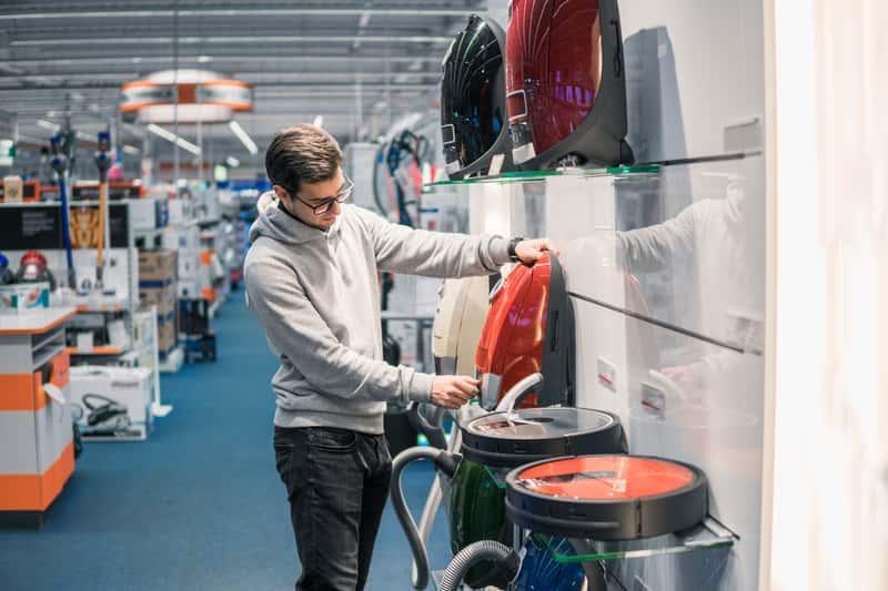 Mężczyzna wybierający odkurzacz Philips w sklepie, a także popularne modele odkurzaczy Philps, opinie oraz ceny
