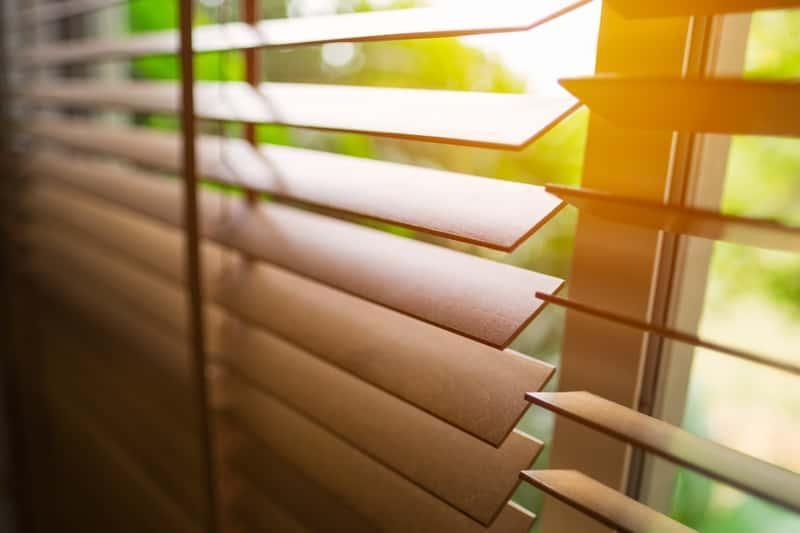 Zakurzone żaluzje drewniane wiszące na oknie, a także informacje, jak czyścić żaluzje drewniane, aluminiowe i bambusowe
