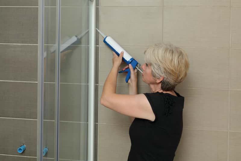 Kobieta uszczelniająca kabinę prysznicową silikonem krok po kroku, a także jak uszczelnić kabinę prysznicową