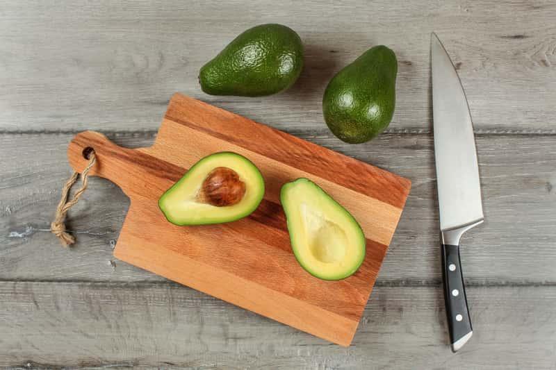 Deska do krojenia na której leżą warzywa i awokado, a także rodzaje desek do krojenia, materiały oraz najlepsze porady dla kucharzy