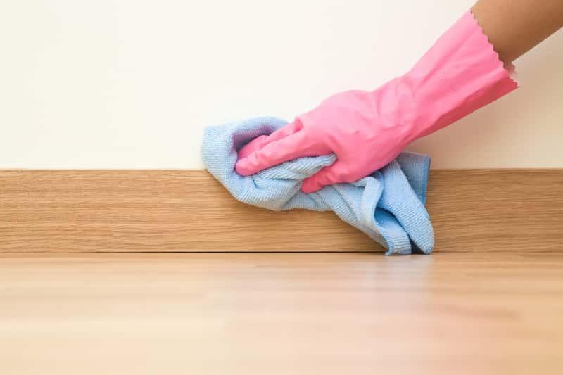 Kobieta myjąca ścianę krok po kroku, a także informacje jak i czym umyć ścianę