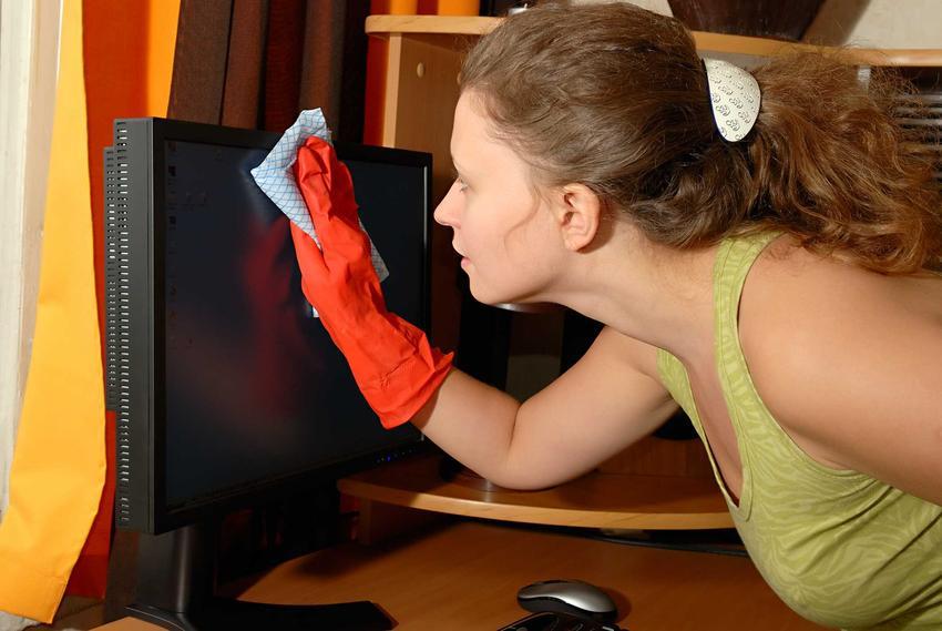 Kobieta podczas czyszczenia monitora z kurzu krok po kroku, a także informacje, czym i jak czyścić monitor krok po kroku
