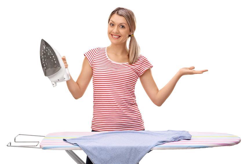 Kobieta trzymająca żelazko w ręce nad deską do prasowania, a także najlepsze deski do prasowania w Biedronce i Lidlu