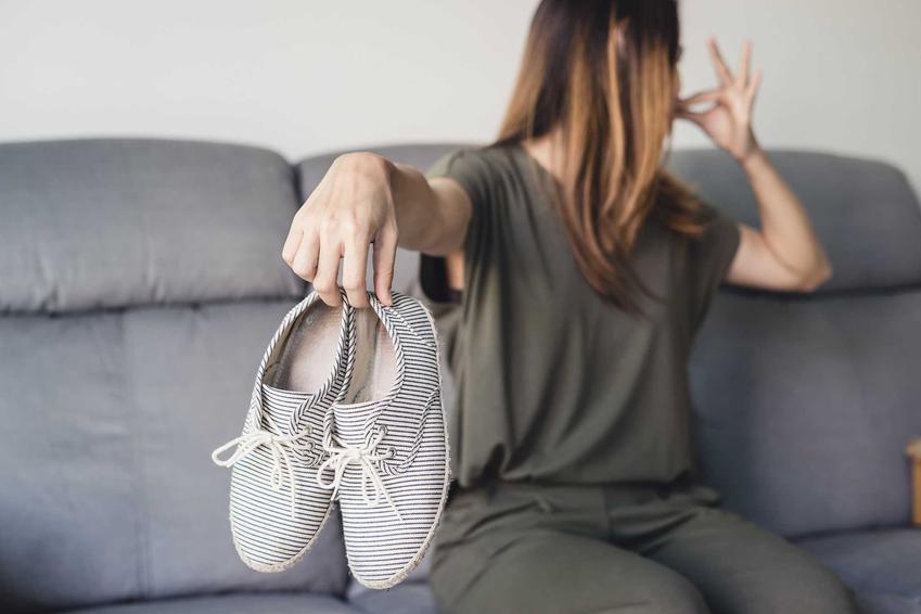 Kobieta z butami zatykająca nos, czyli smród z butów i jak się go pozbyć, sposoby na usuwanie nieprzyjemnego zapachu