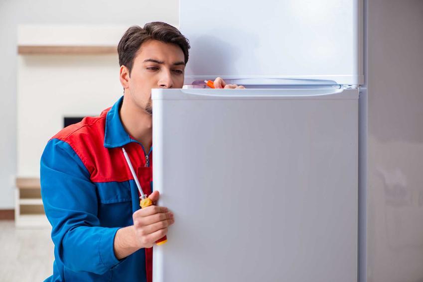 Mężczyzna podczas naprawy lodówki, a także samodzielna naprawda lodówki bez tajemnic, najczęstsze problemy