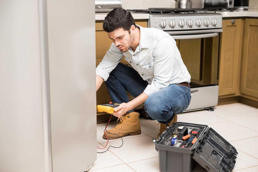 Mężczyzna podczas naprawy lodówki, a także samodzielna naprawda lodówki, czyli awarie, które można naprawić samodzielnie