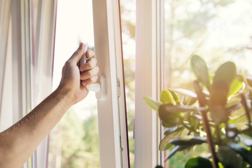 Dłoń na klamce uchylonego okna. Sposoby na wilgoć na szybach i parowanie okien przy niedostatecznej wentylacji w domu