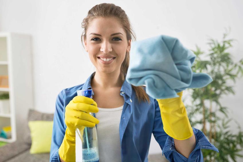 Kobieta myjąca okna za pomocą ściereczki z mikrofibry i płynu. Ścierki i ściereczki do mycia okien polecane do zakupu.