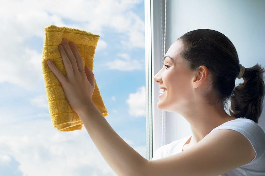 Kobieta myjąca szyby okien za pomocą ściereczki z mikrofibry. Ścierki i ściereczki do mycia okien polecane na rynku.