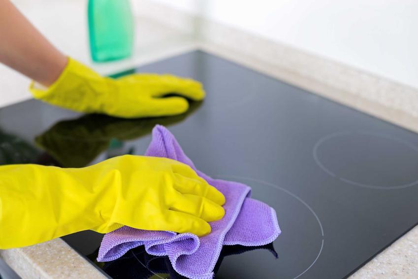 Kobieta podczas czyszczenia płyty indukcyjnej oraz porady, jak czyścić płytę indukcyjną i czym - najlepsze preparaty