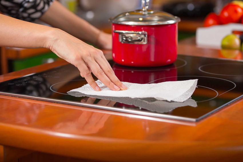 Kobieta podczas czyszczenia płyty indukcyjnej oraz porady, jak czyścić płytę indukcyjną