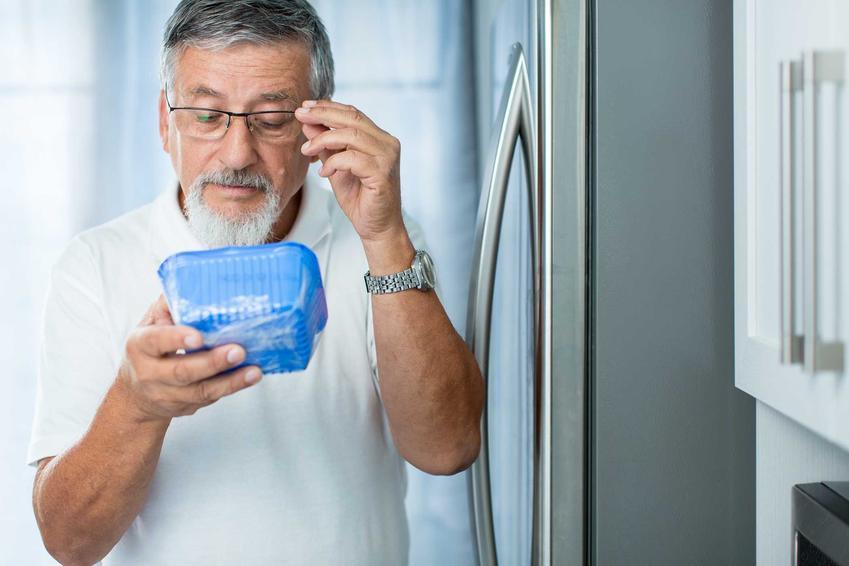 Mężczyzna starający się wyeliminować pleśń w lodówce oraz porady i najlepsze sposoby, jak usunąć pleśń z lodówki