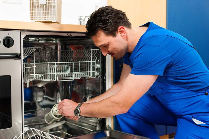 Mężczyzna podczas podłączania zmywarki oraz porady, jak podłączyć zmywarkę do wody, czyli najlepsza instrukcja