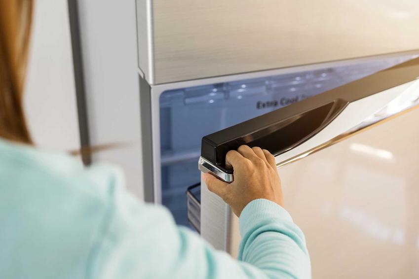 Kobieta otwierająca drzwi lodówki Haier oraz porady, która lodówka Haier będzie najlepsza wraz z cenami