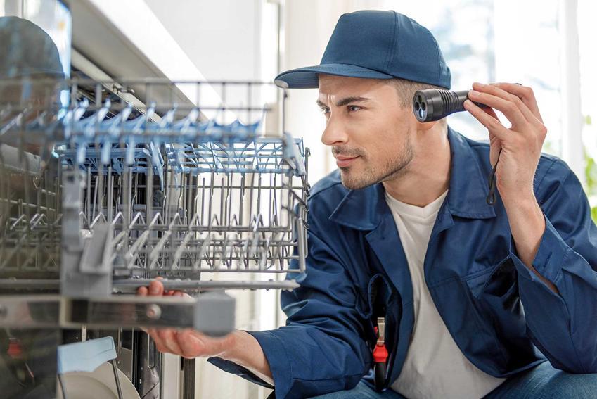Mężczyzna podczas naprawy zmywarki, gdyż zmywarka nie domywa naczyń lub nie myje naczyń dokładnie oraz najważniejsze przyczyny