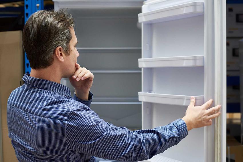 Mężczyzna w sklepie oglądający lodówki Sharp, a także polecane modele, w tym lodówka Sharp side by side