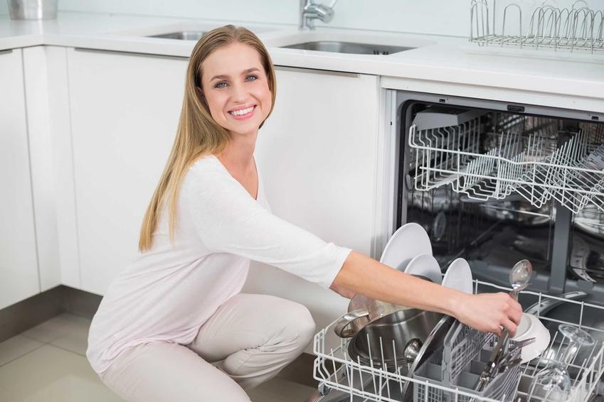Uśmiechnięta kobieta wkładająca naczynia do zmywarki oraz zmywarka Hotpoint Ariston i polecane modele wraz z cenami