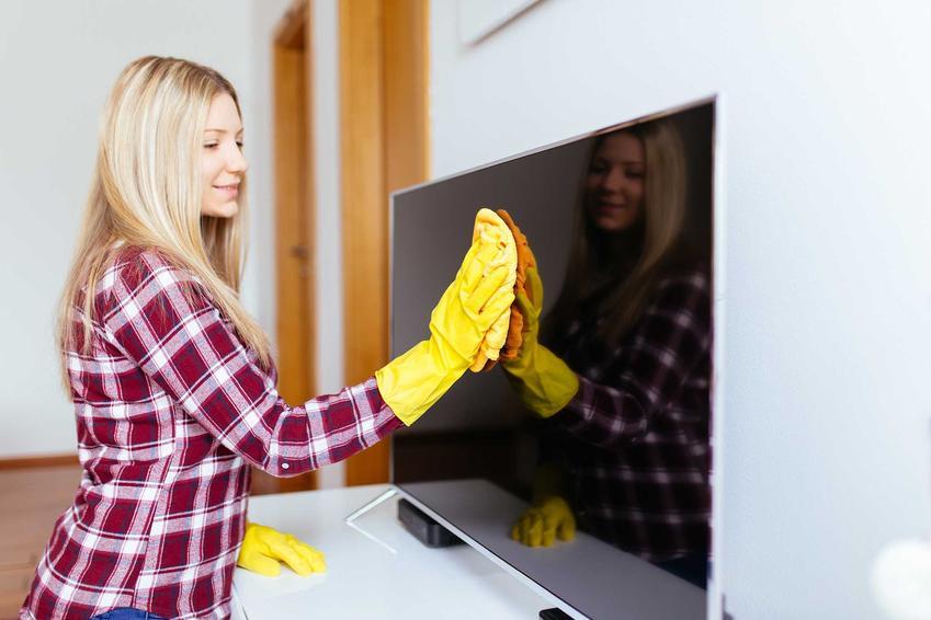 Kobieta, która czyści ekran telewizora plazmowego oraz porady, jak i jakim środkiem umyć ekran telewizora LED