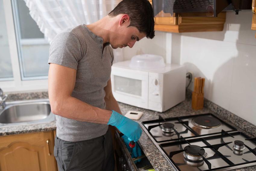 Mężczyzna wykonujący czyszczenie dysz w kuchence gazowej oraz czyszczenie palników krok po kroku